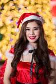 Pretty Asian girl in Santa costume for Christmas with night ligh — Stock Photo