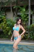 Sexy girl in blue bikini at pool side — Stock Photo