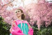 Hanbok: the traditional Korean dress and beautiful Asian girl with sakura — Stock Photo