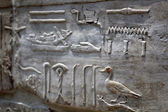 Egyptian figures and hieroglyphics on stone relief — Stock Photo