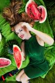Beautiful girl in the grass with watermelons — Stock Photo