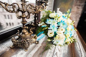 Beautiful wedding bouquet on a wooden table with vintage candlesticks — Stock Photo