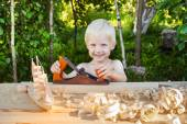 Cutest boy in the workshop of a carpenter planed wood — Stock Photo