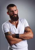 Portrait of handsome bearded man standing with crossed arms, is — Stock Photo