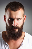 Portrait of handsome bearded man standing, isolated on grey bac — Stock Photo