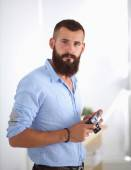 Young beard man holding a camera while standing against white b — Stock Photo