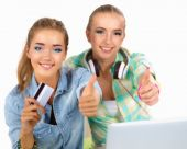 Two young women sitting with laptop  and credit cart showing ok — Foto de Stock