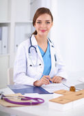 Beautiful young smiling female doctor sitting at the desk and w — Stok fotoğraf