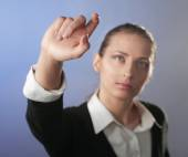 Portrait of a young woman showing something, isolated on grey — Stock Photo