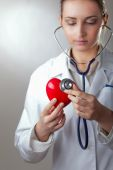 Doctor with stethoscope examining red heart, isolated on grey background — Stockfoto