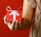 Female hand holding gift box isolated on red — Stock Photo