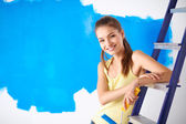 Happy beautiful young woman doing wall painting, sitting on ladder — Zdjęcie stockowe