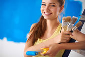 Happy beautiful young woman doing wall painting, standing near ladder — Stockfoto