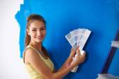 Young beautiful woman holding color palette , standing near wall. — Stock Photo