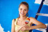 Glad vacker ung kvinna gör väggmålning, stående nära stege — Stockfoto