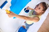 Gerne schöne junge frau tun, wandmalerei, stehend auf leiter — Stockfoto