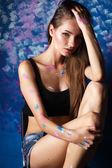 Mladá žena, sedící u malování zdi — Stock fotografie