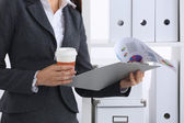Businesswoman with folders and cup of coffee, standing in office — Stockfoto