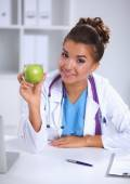 Female doctor hand holding a green apple, sitting at the desk — 图库照片