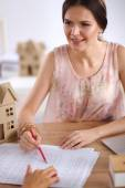 Portrait of female architect with blueprints at desk in office — Stockfoto