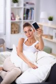 Happy brunette taking a photo of herself with her mobile phone in  bedroom — Stock Photo