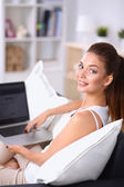 Young beautiful woman using a laptop computer at home — Stock Photo
