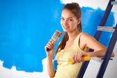 Szczęśliwy piękna młoda kobieta robi malarstwa ściennego, siedząc na drabinie — Zdjęcie stockowe