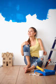 Portrait of female painter sitting on floor near wall after paintingand holding a cup — Stock Photo
