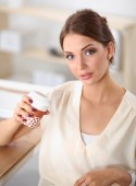 Beautiful  businesswoman enjoying coffee in bright office — Stock Photo