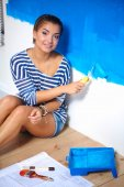 Happy beautiful young woman doing wall painting,sitting on the — Stock Photo