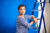 Happy beautiful young woman doing wall painting, standing on la — Stock Photo