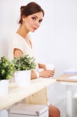 Attractive young businesswoman standing near desk in the office — Foto de Stock