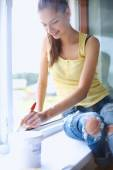 Woman painting wall of an apartment with a paintbrush carefully — Stock Photo