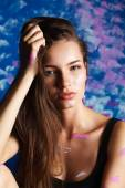Young woman sitting near painting wall — Stock Photo