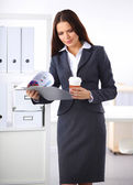 Attractive young businesswoman standing near desk with folder i — ストック写真