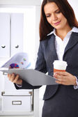 Attractive young businesswoman standing near desk with folder i — Foto de Stock
