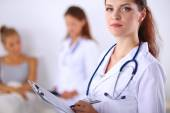 Smiling female doctor with a folder in uniform standing at hosp — Stock Photo