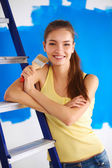 Happy beautiful young woman doing wall painting, standing near — Stock Photo