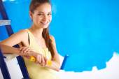 Happy beautiful young woman doing wall painting, sitting on lad — Stock Photo