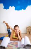 Young woman lying on the floor and looking at blueprint of new — Stockfoto