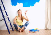 Portrait of female painter sitting on floor near wall after pai — Stock Photo