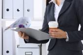 Businesswoman with folders and cup of coffee, standing in offic — Stok fotoğraf