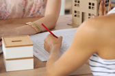 Portrait of female architect with blueprints at desk in office — Stock Photo