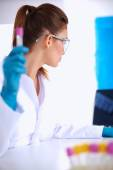 Woman researcher is surrounded by medical vials and flasks, iso — Stock Photo