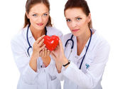 Two woman doctor holding a red heart, isolated on white background — Stock Photo