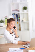 Young businesswoman sitting at the desk and talking on phone — Stock Photo