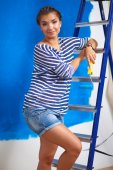 Happy beautiful young woman doing wall painting, standing on ladder — Stock Photo