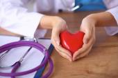 Young doctor with red heart symbol sitting at desk isolated — Stock Photo