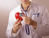 A doctor with stethoscope examining red heart, isolated on grey  background — Stock Photo