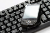 Business concept - a mobile phone over a keyboard — Stock Photo